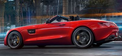 Side view of red overseas Mercedes Benz AMG GT Roadster with top down.
